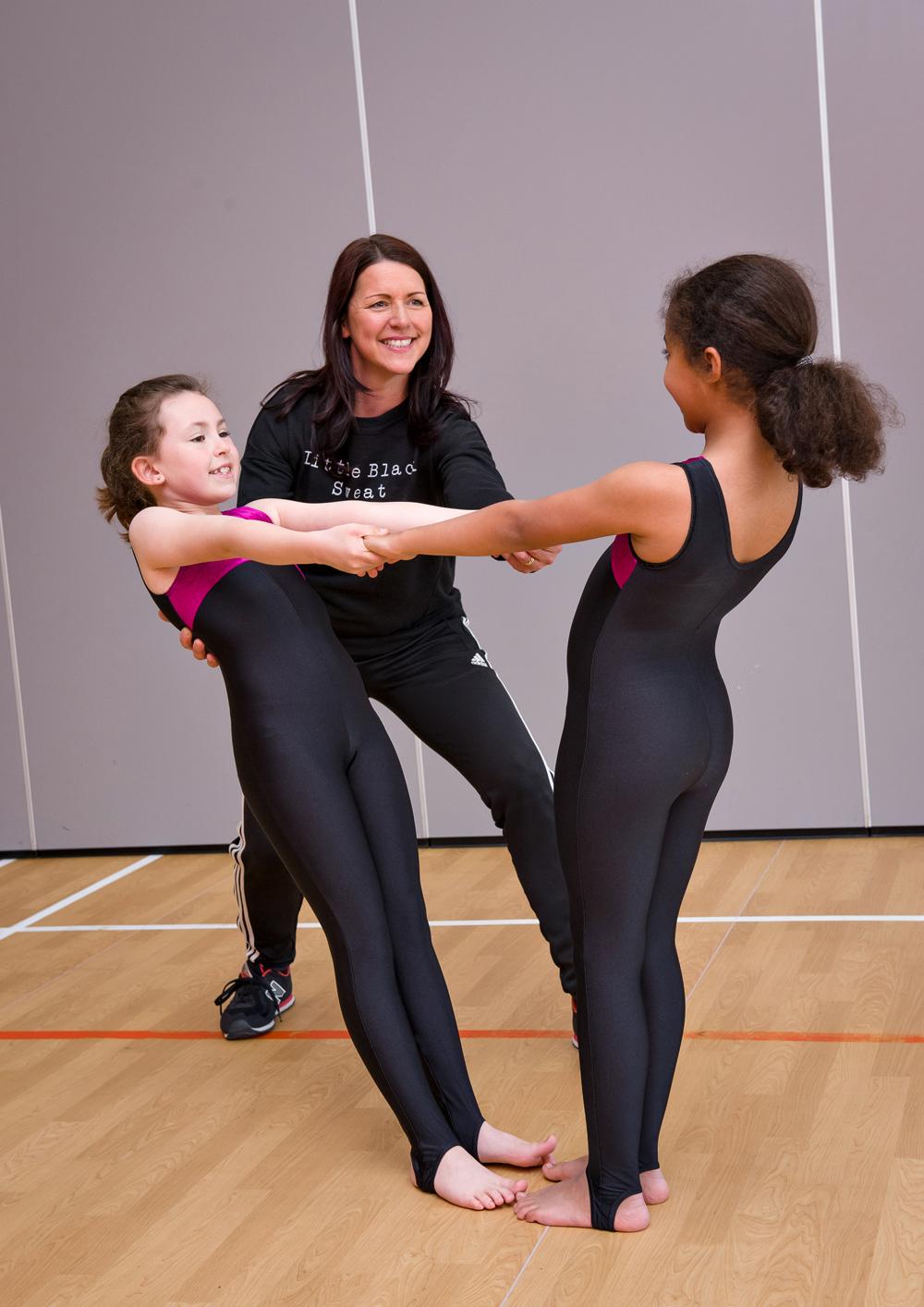 Mrs Bradley teaching two girls gymnastics